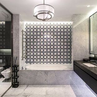 This is an example of a contemporary ensuite bathroom in Moscow with a submerged bath, a wall mounted toilet, a submerged sink, grey floors, flat-panel cabinets, black cabinets and an enclosed toilet.