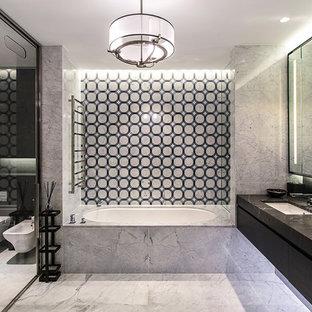 Свежая идея для дизайна: главная ванная комната в современном стиле с полновстраиваемой ванной, инсталляцией, врезной раковиной, серым полом, плоскими фасадами и черными фасадами - отличное фото интерьера