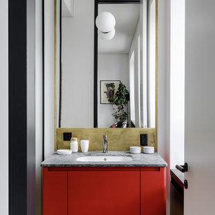 Immagine di una stanza da bagno contemporanea con pareti bianche, pavimento in legno massello medio, pavimento marrone, ante lisce, ante rosse, lavabo sottopiano e top grigio