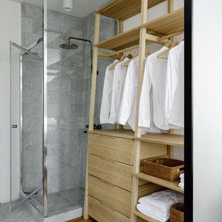 Immagine di una stanza da bagno con doccia design con doccia ad angolo, piastrelle grigie, pareti bianche, pavimento in legno massello medio, pavimento marrone e porta doccia a battente