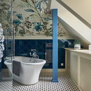 Klassisches Badezimmer En Suite mit Lamellenschränken, beigen Schränken, freistehender Badewanne, Wandtoilette, blauen Fliesen, bunten Wänden, Unterbauwaschbecken und buntem Boden in Sonstige