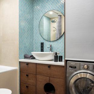Diseño de cuarto de baño principal, actual, pequeño, con armarios con paneles lisos, puertas de armario marrones, bañera encastrada sin remate, sanitario de pared, baldosas y/o azulejos azules, baldosas y/o azulejos en mosaico, paredes beige, suelo de baldosas de porcelana, lavabo encastrado, encimera de acrílico, suelo gris, ducha con cortina y encimeras blancas
