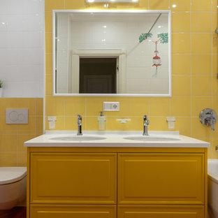 Foto di una stanza da bagno per bambini chic con ante con bugna sagomata, ante gialle, vasca ad alcova, vasca/doccia, WC sospeso, piastrelle bianche, piastrelle gialle, pareti multicolore, lavabo sottopiano e top bianco
