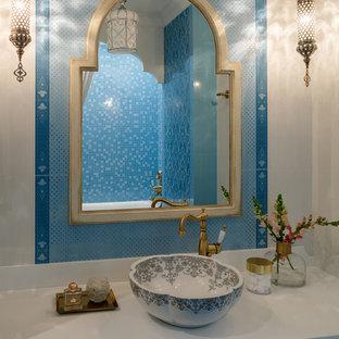 Esempio di una stanza da bagno etnica di medie dimensioni con ante con bugna sagomata, ante turchesi, piastrelle blu, piastrelle in ceramica, lavabo a bacinella e top in superficie solida