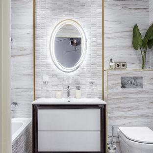 Свежая идея для дизайна: главная ванная комната в современном стиле с плоскими фасадами, белыми фасадами, ванной в нише, душем над ванной, инсталляцией, монолитной раковиной и серым полом - отличное фото интерьера