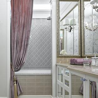 На фото: ванная комната в классическом стиле с фасадами с утопленной филенкой, белыми фасадами, ванной в нише, душем над ванной, серой плиткой, бежевым полом, шторкой для ванной, полом из мозаичной плитки и серыми стенами с