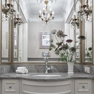 На фото: ванные комнаты в классическом стиле с фасадами с утопленной филенкой, белыми фасадами, врезной раковиной, серой плиткой, керамической плиткой, мраморной столешницей и серыми стенами