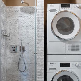 Inredning av ett modernt badrum med dusch, med en dusch i en alkov, grå kakel, beige väggar, grått golv och dusch med gångjärnsdörr