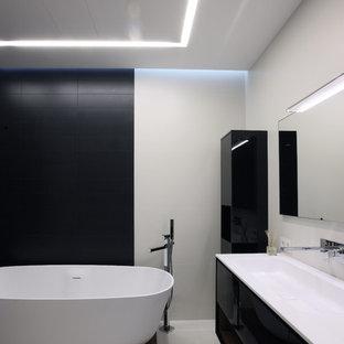 Источник вдохновения для домашнего уюта: главная ванная комната в современном стиле с раковиной с несколькими смесителями, плоскими фасадами, черными фасадами, отдельно стоящей ванной и белыми стенами