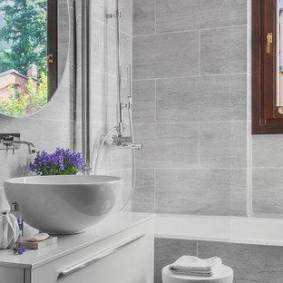 Неиссякаемый источник вдохновения для домашнего уюта: главная ванная комната в современном стиле с плоскими фасадами, белыми фасадами, ванной в нише, серой плиткой, настольной раковиной и белой столешницей