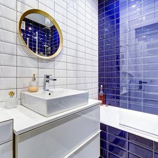 На фото: ванные комнаты в современном стиле с плоскими фасадами, белыми фасадами, ванной в нише, душем над ванной, синей плиткой, белой плиткой, плиткой кабанчик, белыми стенами, душевой кабиной, настольной раковиной и открытым душем