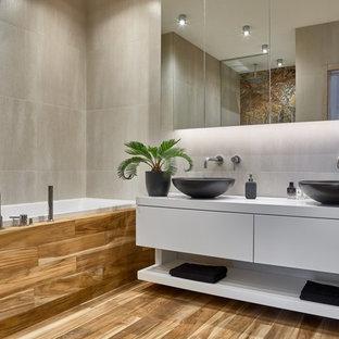 Идея дизайна: главная ванная комната в современном стиле с плоскими фасадами, белыми фасадами, серой плиткой, настольной раковиной, коричневым полом, накладной ванной и серыми стенами