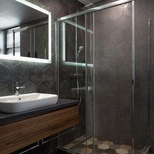 На фото: большая ванная комната в современном стиле с плоскими фасадами, темными деревянными фасадами, угловым душем, черной плиткой, керамической плиткой, полом из керамической плитки, душевой кабиной, накладной раковиной, столешницей из искусственного камня, разноцветным полом, душем с раздвижными дверями и серой столешницей с