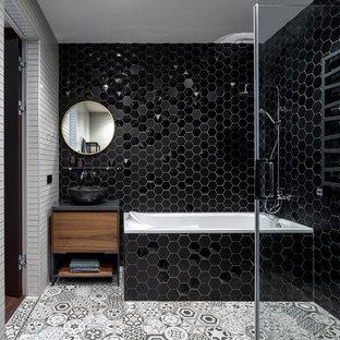 Неиссякаемый источник вдохновения для домашнего уюта: большая главная ванная комната в современном стиле с плоскими фасадами, керамической плиткой, полом из керамической плитки, столешницей из искусственного камня, серым полом, серой столешницей, угловой ванной, черной плиткой, настольной раковиной и фасадами цвета дерева среднего тона