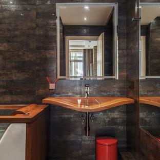 На фото: главная ванная комната в современном стиле с черной плиткой, подвесной раковиной, коричневым полом, столешницей из дерева и коричневой столешницей