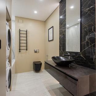 Идея дизайна: большая ванная комната в современном стиле с плоскими фасадами, коричневыми фасадами, ванной в нише, душем над ванной, инсталляцией, черной плиткой, керамогранитной плиткой, бежевыми стенами, полом из керамогранита, душевой кабиной, настольной раковиной, бежевым полом, открытым душем, коричневой столешницей, тумбой под одну раковину и подвесной тумбой