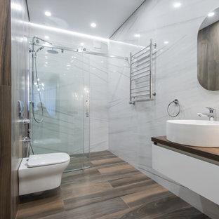 Свежая идея для дизайна: большая ванная комната в современном стиле с плоскими фасадами, белыми фасадами, душем без бортиков, инсталляцией, белой плиткой, керамогранитной плиткой, полом из керамогранита, душевой кабиной, настольной раковиной, столешницей из дерева, коричневым полом, душем с раздвижными дверями, коричневой столешницей, тумбой под одну раковину и подвесной тумбой - отличное фото интерьера