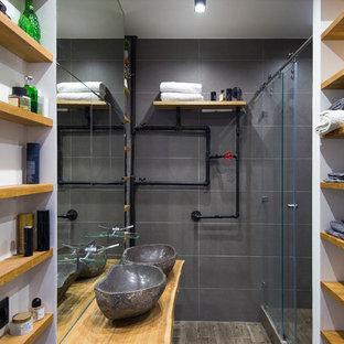 На фото: ванная комната среднего размера в стиле лофт с открытыми фасадами, светлыми деревянными фасадами, душем в нише, серой плиткой, керамогранитной плиткой, полом из керамогранита, душевой кабиной, настольной раковиной, столешницей из дерева, душем с раздвижными дверями, коричневым полом и коричневой столешницей с