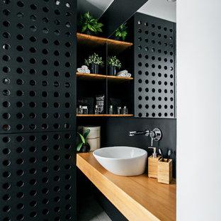 Стильный дизайн: ванная комната в современном стиле с черными стенами, настольной раковиной, серым полом, столешницей из дерева и бежевой столешницей - последний тренд
