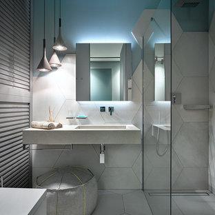 Imagen de cuarto de baño con ducha, actual, con sanitario de pared, baldosas y/o azulejos grises, paredes azules, lavabo integrado y ducha abierta