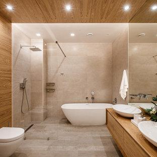 Стильный дизайн: большая главная ванная комната в современном стиле с плоскими фасадами, бежевыми фасадами, отдельно стоящей ванной, душевой комнатой, инсталляцией, бежевой плиткой, керамогранитной плиткой, коричневыми стенами, настольной раковиной, столешницей из дерева, серым полом, открытым душем и бежевой столешницей - последний тренд
