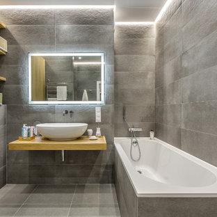 Ispirazione per una stanza da bagno padronale design con nessun'anta, vasca/doccia, WC a due pezzi, piastrelle grigie, lavabo a bacinella, top in legno e top beige