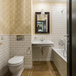 На фото: главная ванная комната в стиле современная классика с ванной в нише, душем над ванной, раздельным унитазом, белой плиткой, плиткой кабанчик, желтыми стенами, подвесной раковиной и коричневым полом