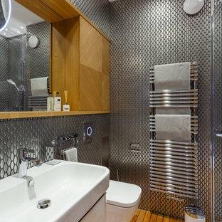 Modernes Duschbad mit flächenbündigen Schrankfronten, weißen Schränken, Wandtoilette, Metallfliesen, braunem Holzboden und Wandwaschbecken in Sonstige