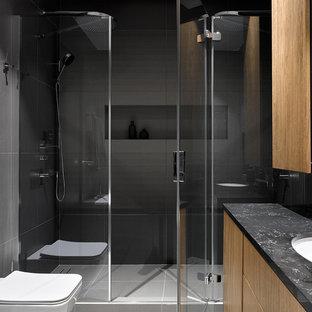 Новые идеи обустройства дома: ванная комната в современном стиле с плоскими фасадами, фасадами цвета дерева среднего тона, серой плиткой, врезной раковиной, серым полом, черной столешницей, душем в нише, инсталляцией и душевой кабиной