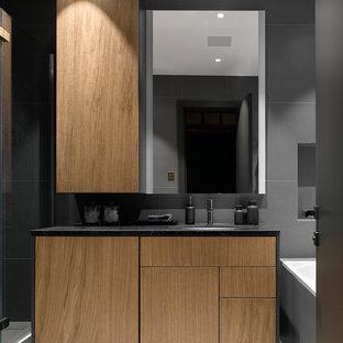 Неиссякаемый источник вдохновения для домашнего уюта: главная ванная комната в современном стиле с плоскими фасадами, фасадами цвета дерева среднего тона, ванной в нише, серой плиткой, врезной раковиной, серым полом и черной столешницей