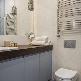 Ejemplo de cuarto de baño contemporáneo, de tamaño medio, con puertas de armario grises, sanitario de pared, baldosas y/o azulejos beige, baldosas y/o azulejos de cerámica, suelo de madera pintada, encimera de madera, suelo marrón, encimeras marrones y lavabo encastrado