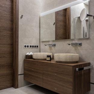 Foto på ett mellanstort funkis brun badrum, med släta luckor, beige kakel, travertinkakel, travertin golv, träbänkskiva, beiget golv, skåp i mellenmörkt trä och ett fristående handfat