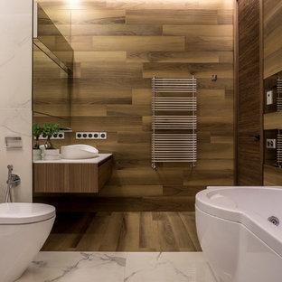 На фото: ванная комната среднего размера в современном стиле с плоскими фасадами, гидромассажной ванной, коричневой плиткой, керамогранитной плиткой, полом из керамогранита, столешницей из искусственного кварца, белой столешницей, фасадами цвета дерева среднего тона, раздельным унитазом, настольной раковиной и коричневым полом с