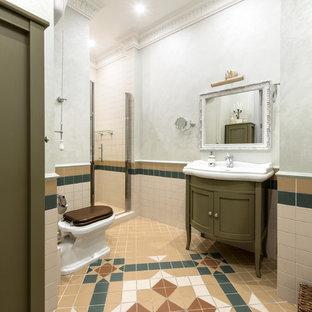 Неиссякаемый источник вдохновения для домашнего уюта: маленькая ванная комната в классическом стиле с зелеными фасадами, бежевой плиткой, керамической плиткой, зелеными стенами, полом из керамической плитки, фасадами с утопленной филенкой, душем в нише, раздельным унитазом, душевой кабиной, монолитной раковиной, разноцветным полом и душем с распашными дверями