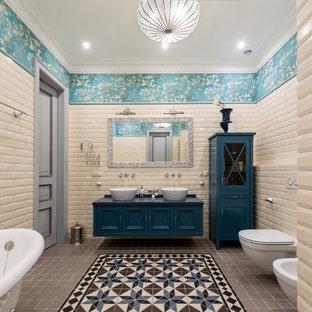 Пример оригинального дизайна: большая ванная комната в классическом стиле с синими фасадами, ванной на ножках, душем в нише, инсталляцией, бежевой плиткой, плиткой кабанчик, синими стенами, полом из керамической плитки, столешницей из искусственного камня, душем с распашными дверями, настольной раковиной и разноцветным полом