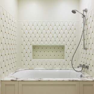 Новый формат декора квартиры: главная ванная комната в стиле современная классика с полновстраиваемой ванной, душем над ванной, белой плиткой, белыми стенами, бежевыми фасадами и открытым душем