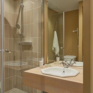 На фото: маленькая ванная комната в современном стиле с угловым душем, бежевой плиткой, душевой кабиной, накладной раковиной и бежевой столешницей