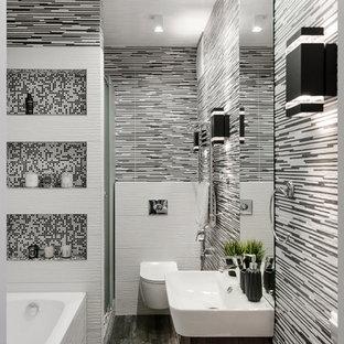 Пример оригинального дизайна: ванная комната в современном стиле с плоскими фасадами, темными деревянными фасадами, ванной в нише, инсталляцией, черно-белой плиткой, разноцветными стенами, душевой кабиной, подвесной раковиной и серым полом