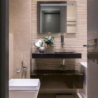 Стильный дизайн: главная ванная комната в современном стиле с плоскими фасадами, черными фасадами, инсталляцией, бежевой плиткой, монолитной раковиной, бежевым полом, черной столешницей, ванной в нише и бежевыми стенами - последний тренд