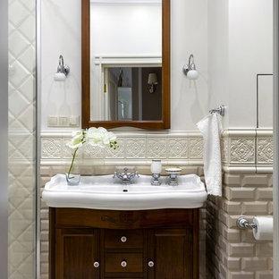 На фото: ванная комната в стиле неоклассика (современная классика) с фасадами в стиле шейкер, темными деревянными фасадами, душем в нише, бежевой плиткой, плиткой кабанчик, белыми стенами, душевой кабиной, накладной раковиной и белым полом
