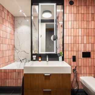 На фото: ванная комната в современном стиле с плоскими фасадами, фасадами цвета дерева среднего тона, полновстраиваемой ванной, инсталляцией, розовой плиткой, керамической плиткой, розовыми стенами, полом из керамогранита, черным полом и монолитной раковиной с