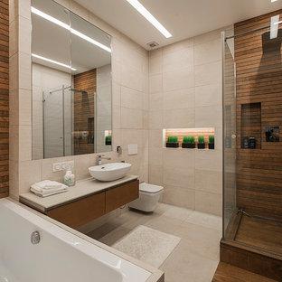 На фото: со средним бюджетом главные ванные комнаты среднего размера в современном стиле с плоскими фасадами, фасадами цвета дерева среднего тона, полновстраиваемой ванной, инсталляцией, бежевой плиткой, керамогранитной плиткой, бежевыми стенами, полом из керамогранита, столешницей из искусственного камня, бежевым полом, душем с распашными дверями, угловым душем и настольной раковиной