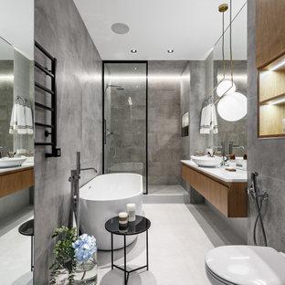 Пример оригинального дизайна: главная ванная комната в современном стиле с плоскими фасадами, фасадами цвета дерева среднего тона, отдельно стоящей ванной, душем в нише, настольной раковиной, серым полом, белой столешницей, тумбой под одну раковину и подвесной тумбой