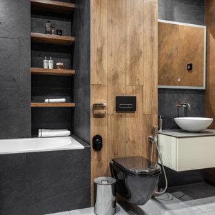 Пример оригинального дизайна: главная ванная комната среднего размера в современном стиле с плоскими фасадами, серыми фасадами, ванной в нише, инсталляцией, серой плиткой, керамогранитной плиткой, полом из керамогранита, настольной раковиной, столешницей из искусственного камня, серым полом, серой столешницей, унитазом, тумбой под одну раковину, подвесной тумбой и угловым душем