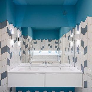 На фото: детская ванная комната в современном стиле с плоскими фасадами, белыми фасадами, синей плиткой, белой плиткой, синими стенами, белым полом и монолитной раковиной