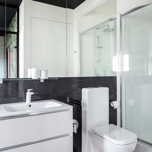 Стильный дизайн: ванная комната в современном стиле с плоскими фасадами, белыми фасадами, душем в нише, черной плиткой, белыми стенами, паркетным полом среднего тона, душевой кабиной, коричневым полом, керамогранитной плиткой, раздельным унитазом и монолитной раковиной - последний тренд