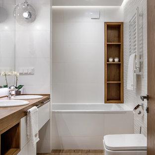 На фото: маленькая главная ванная комната в современном стиле с плоскими фасадами, белыми фасадами, ванной в нише, душем над ванной, инсталляцией, белой плиткой, белыми стенами, полом из керамогранита, столешницей из дерева, накладной раковиной и коричневым полом с