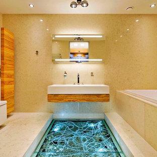 Immagine di una stanza da bagno padronale minimal di medie dimensioni con lavabo sospeso, vasca idromassaggio, bidè, ante beige, piastrelle beige, piastrelle in pietra e top in marmo