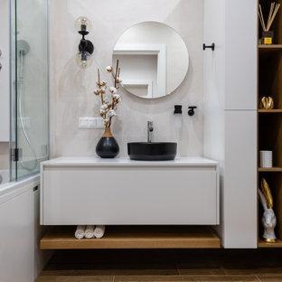 На фото: главная ванная комната в современном стиле с плоскими фасадами, белыми фасадами, ванной в нише, душем над ванной, бежевой плиткой, настольной раковиной, белой столешницей, тумбой под одну раковину и подвесной тумбой