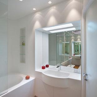 Пример оригинального дизайна: главная ванная комната в современном стиле с плоскими фасадами, белыми фасадами, ванной в нише, монолитной раковиной и коричневым полом